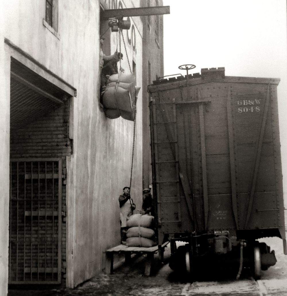 "An exterior view of the Springfield Brewing Company with grain being unloaded from a rail car on the 10th street tracks. The photo probably dates to the mid to late 1930's. Immediately after Prohibition ended in 1933, a new brewery, The Springfield Brewing Company, headed up by Chicago businessman Nicholas A. Schlangen, set up shop in buildings located at 11th and Madison streets. According to a 2009 issue of the magazine Beer Cans & Brewery Collectibles held in Lincoln Library, the new brewery produced its first beer, ""Archer,"" available only on draft, on October 25, 1933. Conrad Engelking became president of the brewery in 1934 and eventually a beer was named after him: ""Engelking's"". The firm embraced marketing in a big way and did contract brewing for other brands shipped out of state. The brewery ceased operations in 1947.  Photograph courtesy Sangamon Valley Collection at Lincoln Library"