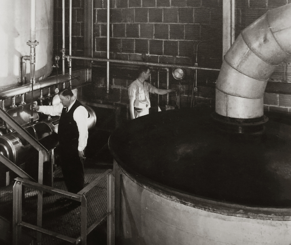 "Working in the brewhouse with a large kettle at right at the Springfield Brewing Company. The photo probably dates to the mid to late 1930's. Immediately after Prohibition ended in 1933, a new brewery, The Springfield Brewing Company, headed up by Chicago businessman Nicholas A. Schlangen, set up shop in buildings located at 11th and Madison streets. According to a 2009 issue of the magazine Beer Cans & Brewery Collectibles held in Lincoln Library, the new brewery produced its first beer, ""Archer,"" available only on draft, on October 25, 1933. Conrad Engelking became president of the brewery in 1934 and eventually a beer was named after him: ""Engelking's"". The firm embraced marketing in a big way and did contract brewing for other brands shipped out of state. The brewery ceased operations in 1947.  Photograph courtesy Sangamon Valley Collection at Lincoln Library"