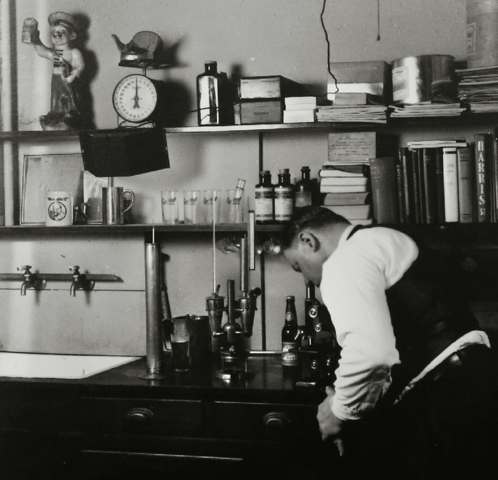 "A Springfield Brewing Company employee previously seen in the brewhouse photograph peers through a microscope in a separate office at the brewery. The photo probably dates to the mid to late 1930's. Immediately after Prohibition ended in 1933, a new brewery, The Springfield Brewing Company, headed up by Chicago businessman Nicholas A. Schlangen, set up shop in buildings located at 11th and Madison streets. According to a 2009 issue of the magazine Beer Cans & Brewery Collectibles held in Lincoln Library, the new brewery produced its first beer, ""Archer,"" available only on draft, on October 25, 1933. Conrad Engelking became president of the brewery in 1934 and eventually a beer was named after him: ""Engelking's"". The firm embraced marketing in a big way and did contract brewing for other brands shipped out of state. The brewery ceased operations in 1947.  Photograph courtesy Sangamon Valley Collection at Lincoln Library"