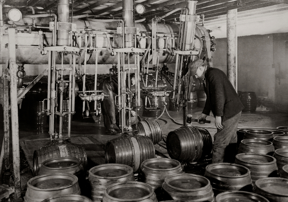 "A worker uses a mallet to tap a freshly-filled beer keg at the Springfield Brewing Company. The photo probably dates to the mid to late 1930's. Immediately after Prohibition ended in 1933, a new brewery, The Springfield Brewing Company, headed up by Chicago businessman Nicholas A. Schlangen, set up shop in buildings located at 11th and Madison streets. According to a 2009 issue of the magazine Beer Cans & Brewery Collectibles held in Lincoln Library, the new brewery produced its first beer, ""Archer,"" available only on draft, on October 25, 1933. Conrad Engelking became president of the brewery in 1934 and eventually a beer was named after him: ""Engelking's"". The firm embraced marketing in a big way and did contract brewing for other brands shipped out of state. The brewery ceased operations in 1947.  Photograph courtesy Sangamon Valley Collection at Lincoln Library"
