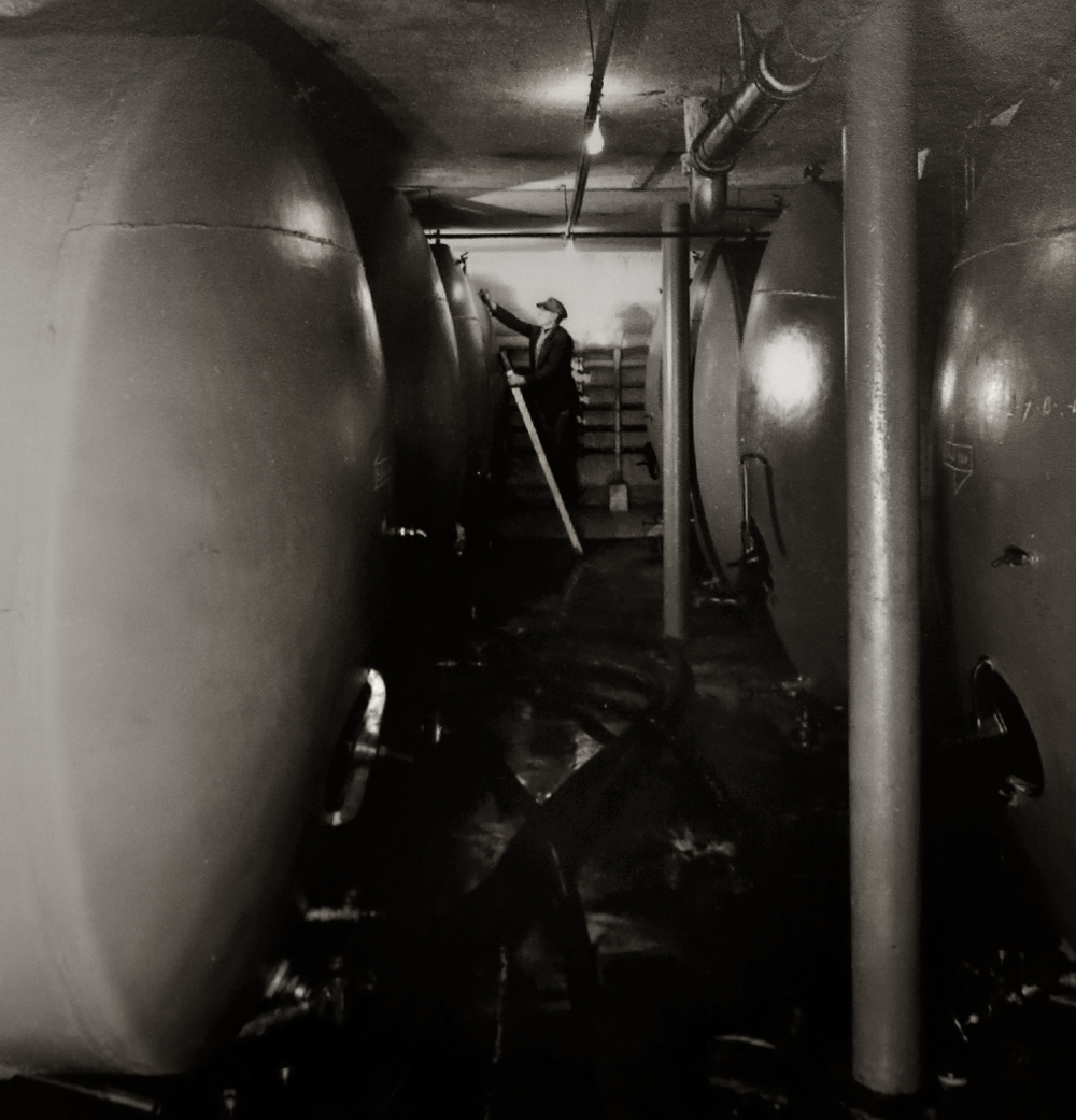 "A worker checks one of the large metal beer storage and aging tanks at the Springfield Brewing Company. The photo probably dates to the mid to late 1930's. Immediately after Prohibition ended in 1933, a new brewery, The Springfield Brewing Company, headed up by Chicago businessman Nicholas A. Schlangen, set up shop in buildings located at 11th and Madison streets. According to a 2009 issue of the magazine Beer Cans & Brewery Collectibles held in Lincoln Library, the new brewery produced its first beer, ""Archer,"" available only on draft, on October 25, 1933. Conrad Engelking became president of the brewery in 1934 and eventually a beer was named after him: ""Engelking's"". The firm embraced marketing in a big way and did contract brewing for other brands shipped out of state. The brewery ceased operations in 1947.  Photograph courtesy Sangamon Valley Collection at Lincoln Library"