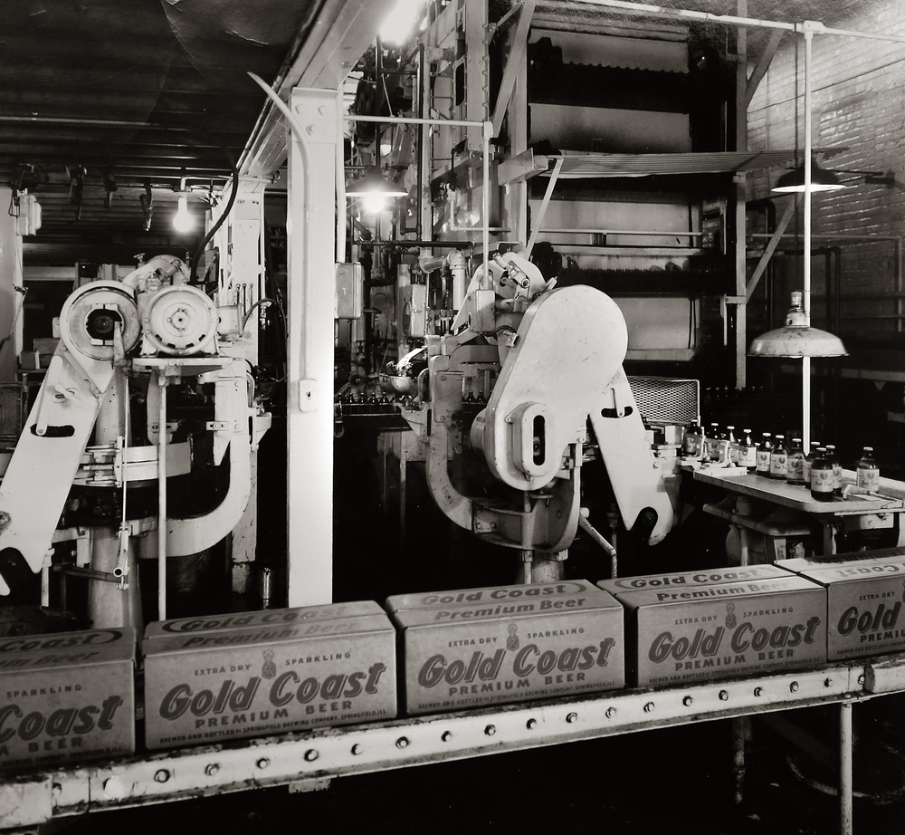 "A photograph taken by Springfield's Mercury Commerical Photographers shows freshly packed cases of Gold Coast Premium Beer coming off the line at the Springfield Brewing Company. The photo probably dates to 1940's. Immediately after Prohibition ended in 1933, a new brewery, The Springfield Brewing Company, headed up by Chicago businessman Nicholas A. Schlangen, set up shop in buildings located at 11th and Madison streets. According to a 2009 issue of the magazine Beer Cans & Brewery Collectibles held in Lincoln Library, the new brewery produced its first beer, ""Archer,"" available only on draft, on October 25, 1933. Conrad Engelking became president of the brewery in 1934 and eventually a beer was named after him: ""Engelking's"". The firm embraced marketing in a big way and did contract brewing for other brands shipped out of state. The brewery ceased operations in 1947.  Photograph courtesy Sangamon Valley Collection at Lincoln Library"