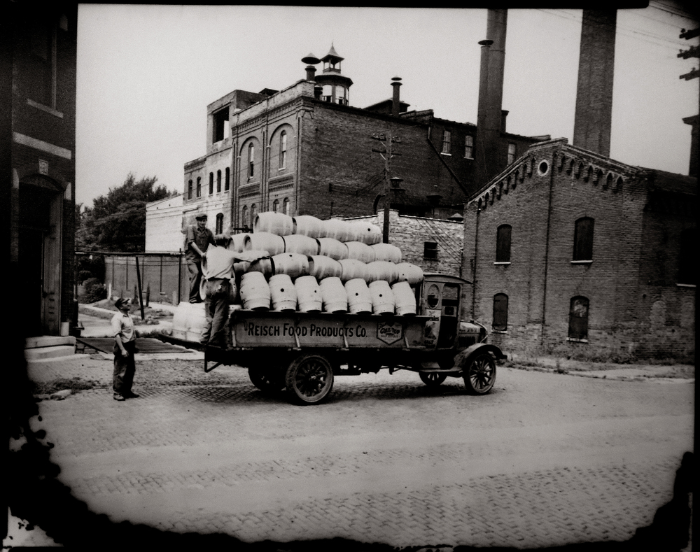 "Workers stand on the back end of a truck loaded with empty wooden beer kegs, with ""Reisch Food Products Co."" painted on the side in front of the Reisch Brewery complex. The photo probably dates to the early 1930's, when the brewery was transitioning back to brewing beer after the end of Prohibition in 1933. Photograph courtesy Sangamon Valley Collection at Lincoln Library"