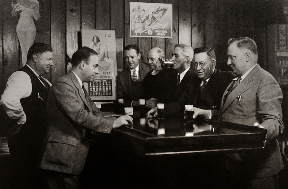 "Springfield Brewing Company executives enjoy a cold one in the company's tap room. The photo probably dates to the mid to late 1930's. Immediately after Prohibition ended in 1933, a new brewery, The Springfield Brewing Company, headed up by Chicago businessman Nicholas A. Schlangen, set up shop in buildings located at 11th and Madison streets. According to a 2009 issue of the magazine Beer Cans & Brewery Collectibles held in Lincoln Library, the new brewery produced its first beer, ""Archer,"" available only on draft, on October 25, 1933. Conrad Engelking became president of the brewery in 1934 and eventually a beer was named after him: ""Engelking's"". The firm embraced marketing in a big way and did contract brewing for other brands shipped out of state. The brewery ceased operations in 1947.  Photograph courtesy Sangamon Valley Collection at Lincoln Library"
