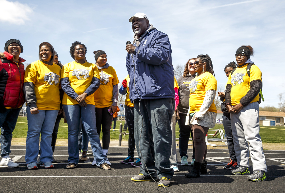 Former Southeast girls track and field coach Thomas McBride is surrounded by his former athletes as they honor him prior to the start of the newly named Thomas McBride Invitational track and field meet at Southeast High School , Saturday, April 9, 2016, in Springfield, Ill. Justin L. Fowler/The State Journal-Register