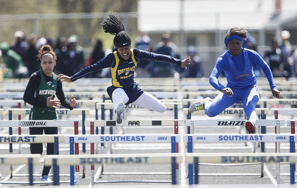 Southeast's Dontavia Howard, center, finished second to East St. Louis' Rokelle Stanley, right, in the 100m Hurdles during the Thomas McBride Invitational track and field meet at Southeast High School , Saturday, April 9, 2016, in Springfield, Ill. Justin L. Fowler/The State Journal-Register