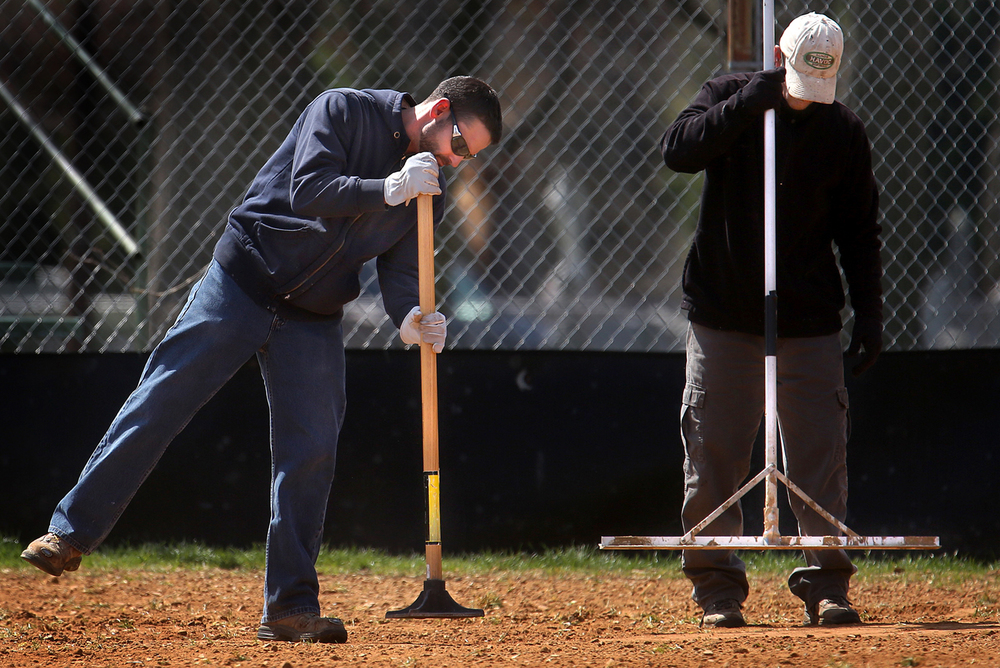 The job of tamping down freshly added and broken-up dirt in the batter's box on either side of home plate in order to make it level and comfortable for players is an art form. Employees Patrick Sawyer at left and Dave LeMasters work as a team on one of the ball diamonds at Lincoln Park Monday while getting it prepped before a softball game between Lanphier High School and New Berlin/Franklin/Waverly on Monday afternoon, April 4, 2016. In addition to high school play, the Park District's Co-Ed Summer Softball recreational league will begin play at Lincoln as well as Iles Park starting on April 13 through June 22. David Spencer/The State Journal Register