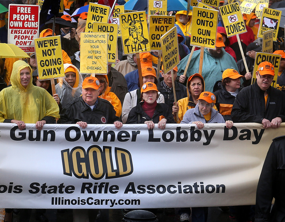Illinois Gun Owner Lobby Day (IGOLD) participants walk down Capitol Ave. in the pouring rain in Springfield early Wednesday afternoon before they headed inside the Capitol Building to lobby their individual state legislators. The Illinois State Rifle Association held their annual Illinois Gun Owner Lobby Day in Springfield on Wednesday, April 6, 2016. A rally at the Prairie Capital Convention Center in Springfield was followed by the march to the Illinois State Capitol building where gun rights supporters lobbied their state legislators in order to protect Second Amendment rights. David Spencer/The State Journal-Register
