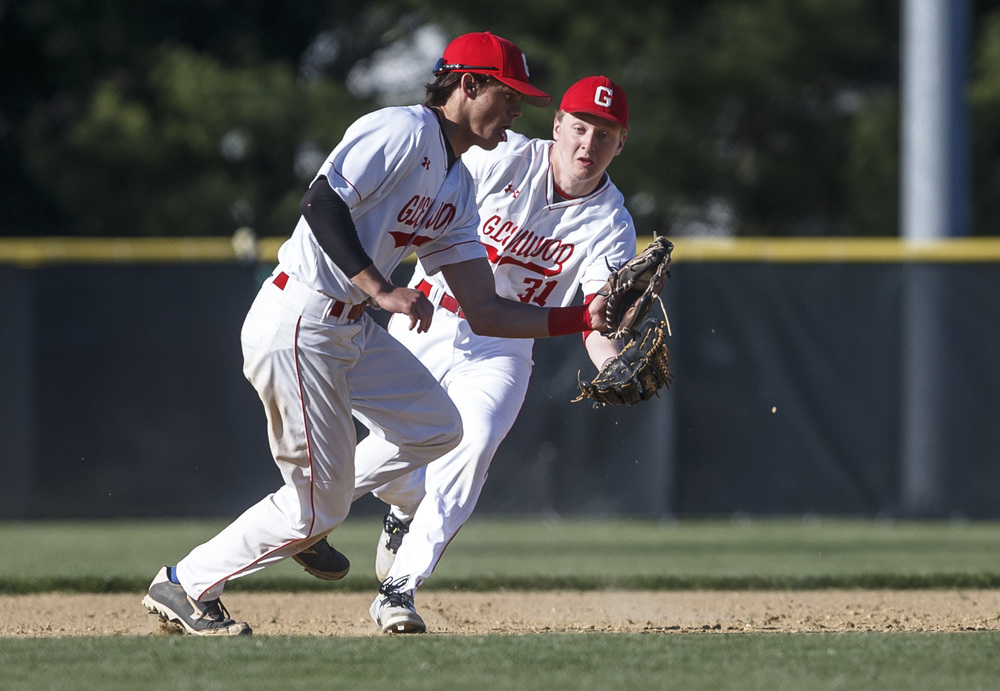 Glenwood's Logan Cody fields a ground ball in front of Graham Bender, but made an errant throw to first trying to get the out against Sacred Heart-Griffin in the fifth inning at Chatham Community Park, Thursday, April 14, 2016, in Chatham, Ill. Justin L. Fowler/The State Journal-Register