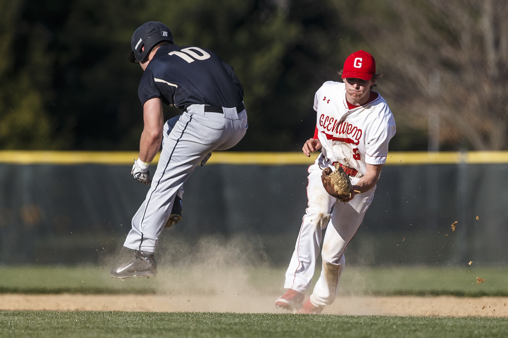 Sacred Heart-Griffin's Sam Sergent leaps over a ground ball fielded by Glenwood's Ryan McAvoy to advance to second in the fifth inning at Chatham Community Park, Thursday, April 14, 2016, in Chatham, Ill. Justin L. Fowler/The State Journal-Register