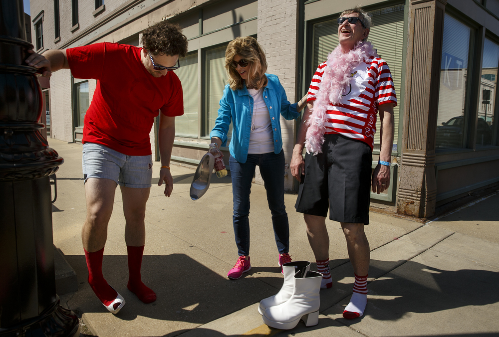 Max Hammer leans back and sighs in relief after removing a pair of tight fitting high heels to exchange for a pair of boots worn by Tony Lucca as they participate in the 10th Annual Walk a Mile in Her Shoes event Saturday, April 16, 2016. Cheri Hammer, center, helped facilitate the exchange. Ted Schurter/The State Journal-Register