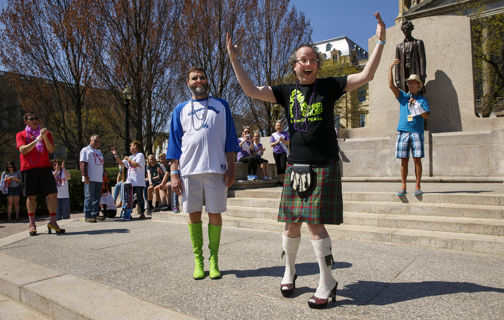 Tom Henehan turns to the crowd after being affirmed by applause as having the best heels during the 10th Annual Walk a Mile in Her Shoes event Saturday, April 16, 2016. Cheri Hammer, center, helped facilitate the exchange. Henehan edged out Mike Ramm and his pair of neon green knee high boots. Ted Schurter/The State Journal-Register