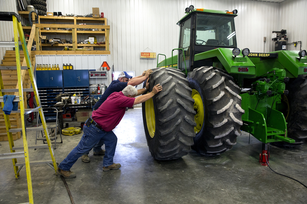 Andy Mason and his son, Cody, push a tire onto its mount in the shop on their farm near Jacksonville Monday, April 11, 2016. To lower costs and help him ease into farming on his own, Cody Mason refurbished a 1989 model John Deere 4-wheel drive tractor. Rich Saal/The State Journal-Register