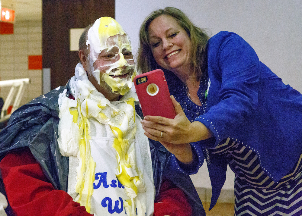 "Dana Mollohan shows a picture of her boss, Kevin England, getting a pie thrown in his face during ""Take a Pie for Y,"" a part of the annual Kick-Off Breakfast for the Strong Kids Scholarship Fund Wednesday, April 13, 2016 at the downtown YMCA. England works at Memorial Medical Center. Rich Saal/The State Journal-Register"