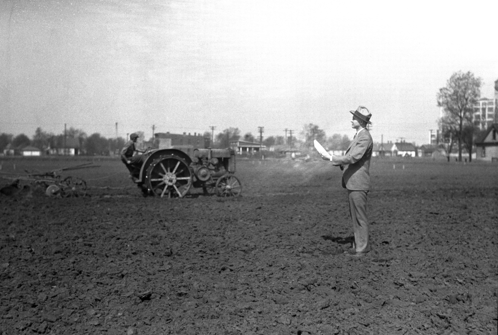 Frank Dillion, Y.M.C.A. secretary, oversees preparation of garden plot for unemployed near C&IM railroad at 19th Street and Moffat Avenue, April 19, 1931. Operating the tractor is James Holzwort. Illinois State Journal glass plate negative/Sangamon Valley Collection at Lincoln Library. All Rights Reserved, The State Journal-Register.  C-98-1149 Neg #1055.