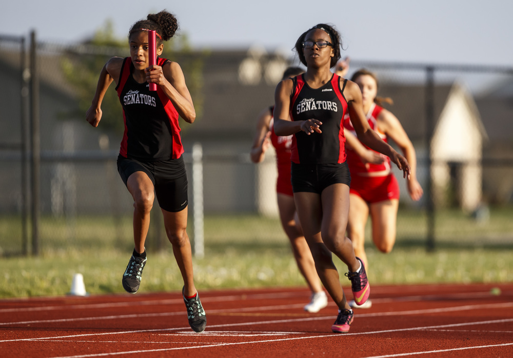 Springfield's Lauren Ferguson, left, takes the baton from Chieme Udaku to run the second leg of the Girls 4x100m Relay during the Co-Ed Titan Invite at Glenwood High School, Friday, April 22, 2016, in Chatham, Ill. Justin L. Fowler/The State Journal-Register