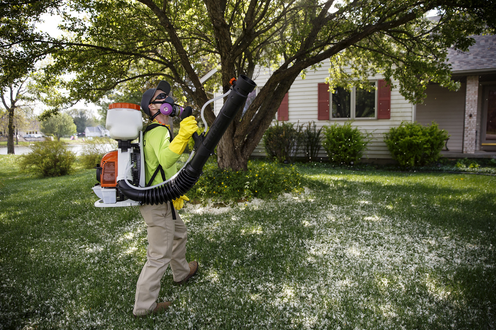 Mosquito Squad employee Brandon Defenbaugh sprays the yard of an Athens home Friday, April 22, 2016. Ted Schurter/The State Journal-Register