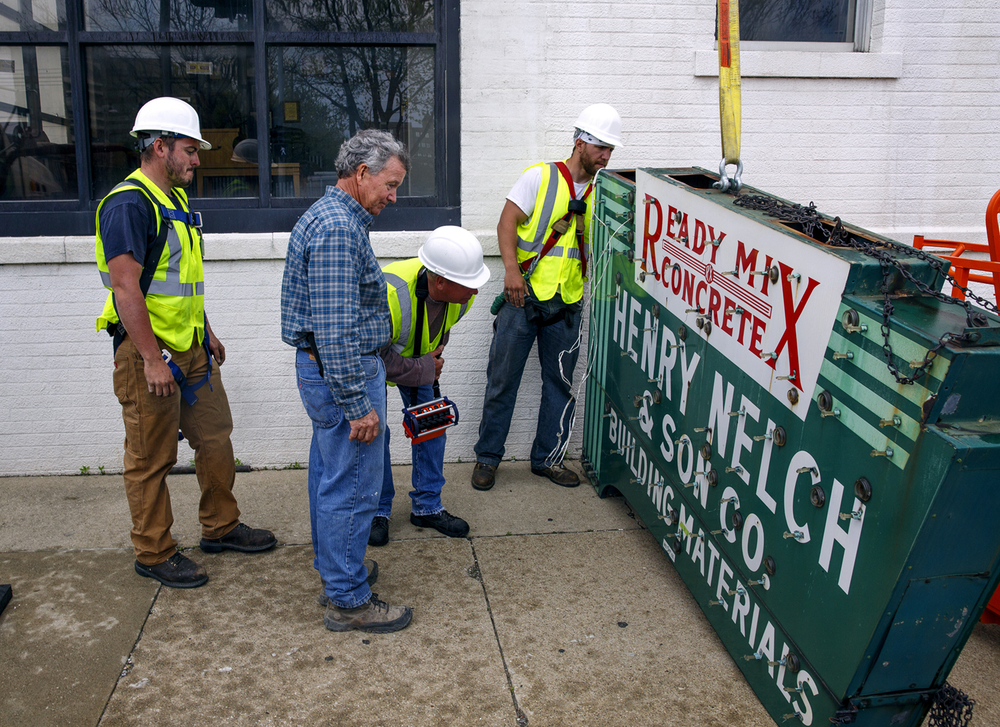 Rob Nelch, center, looks over the sign for his family's former business on Ninth Street after it was removed from the building by Ace Sign Co. employees Tommy Sheppard, Jr., left, Donny Walden and Nic Anderson Wednesday, April 20, 2016. Nelch has donated the sign to the Ace company's antique sign museum. Nelch & Son closed in early 2015 after nearly 120 years in business and Rob Nelch now serves as local yard manager for Chicago-based brick and masonry company Illinois Brick Co., which has taken over the site. Rich Saal/The State Journal-Register
