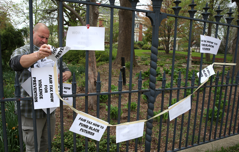 An Executive Mansion employee removes signs supporting the Fair Tax bills before the Illinois General Assembly that were taped to the outside of the governor's residence in Springfield on Wednesday, April 20, 2016 during a protest by union and community groups organized through the The Grassroots Collaborative of Chicago. David Spencer/The State Journal-Register