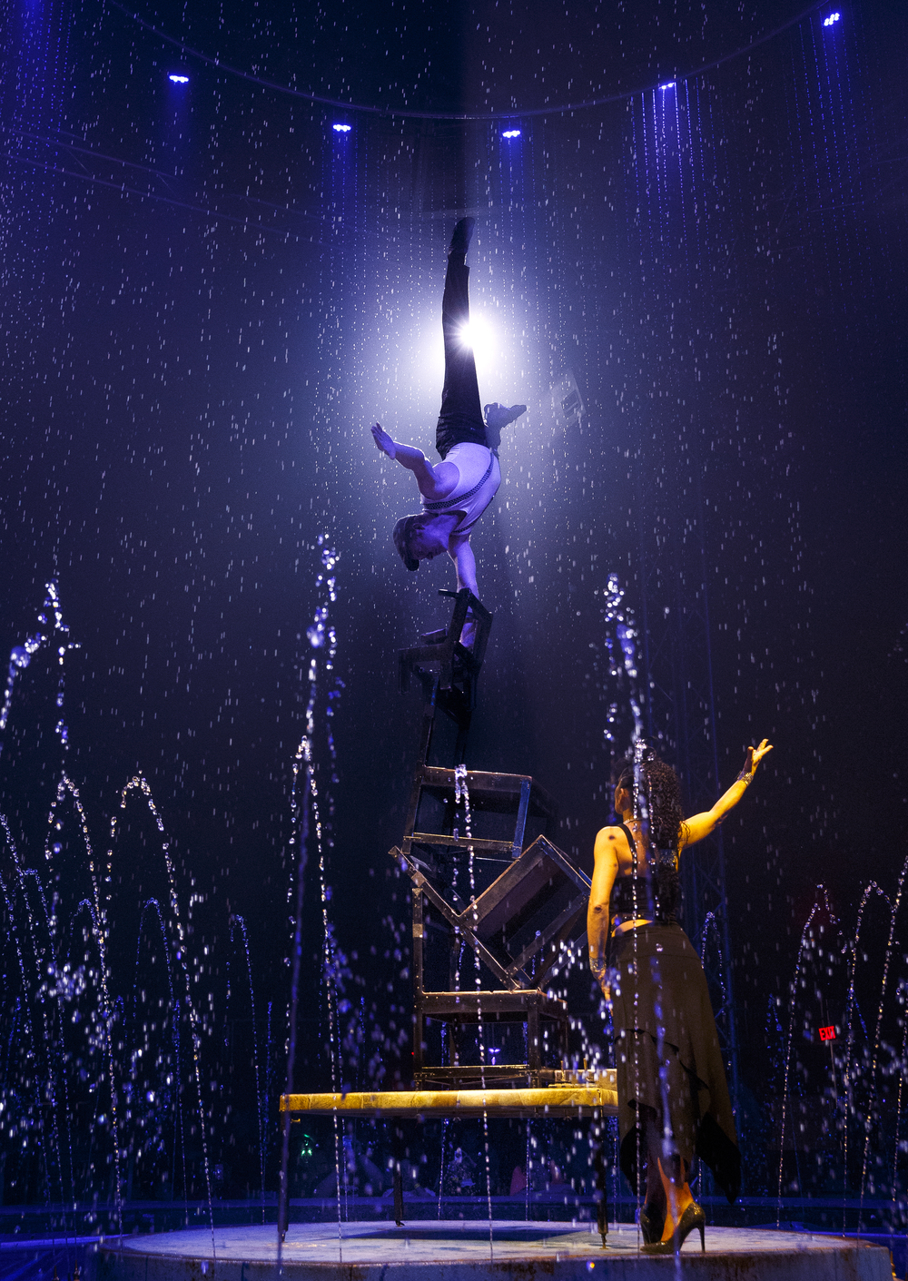 "Dana Patrana  watches as Gimmi Fornaciari performs a one-armed handstand on a stack of chairs during an afternoon performance of ""Aquatic Spectacular"" by the Cirque Italia Sunday, May 1, 2016. The travelling show features a 35,000 gallon water stage, colorful water curtain and dancing fountains. Ted Schurter/The State Journal-Register"