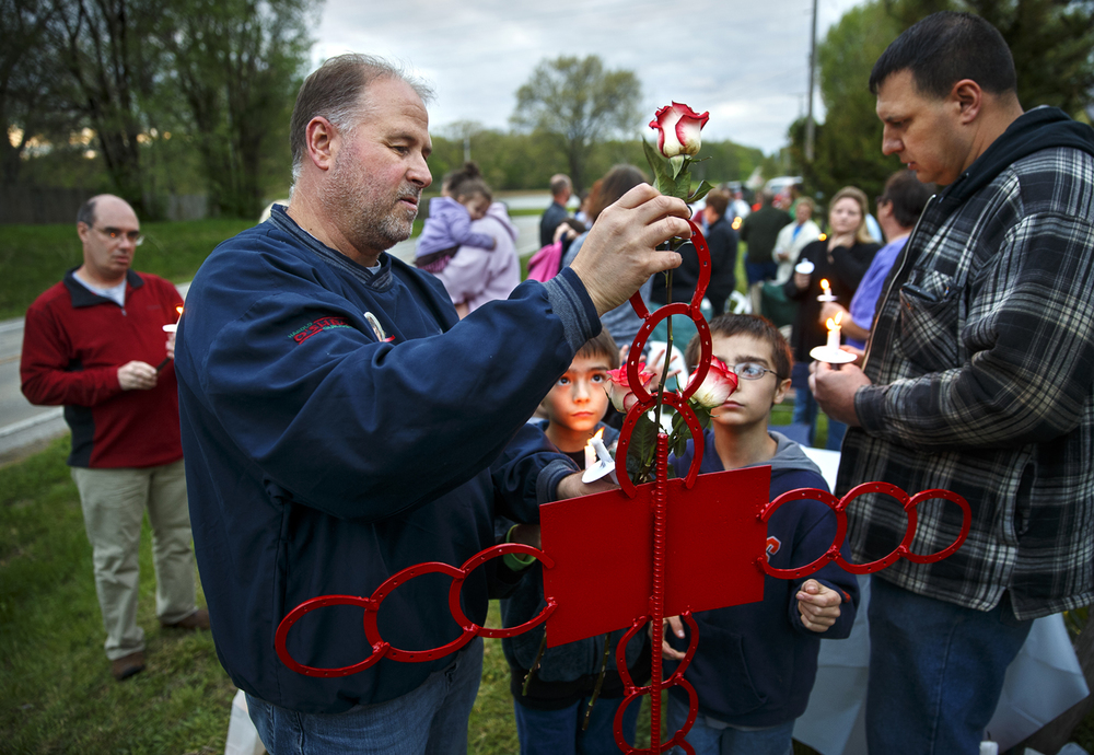 Chris Reavis places a rose on a red cross during a vigil Thursday, April 28, 2016 to observe the 25th anniversary of the deaths of Dale Allan Harper, Reavis' brother, Jeffrey Batson and  Sharon Ostenburg along the Mechanicsburg Blacktop. About 40 friends and family members gathered at the crash site, including Batson's brother Jeremy, right.  Ted Schurter/The State Journal-Register