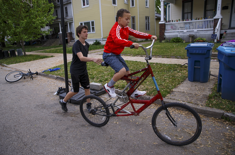 Jaydon Braner helps Rico Parrish get started on a tall bicycle owned by one of his friends in Enos Park Friday, April 29, 2016. Ted Schurter/The State Journal-Register