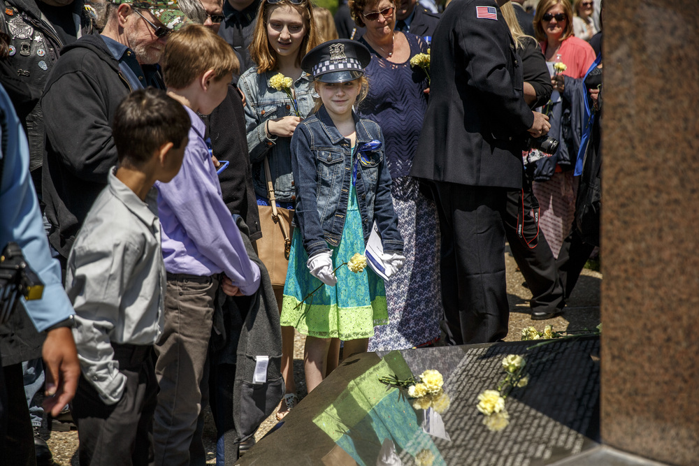 Hannah DeCicco, 11, the niece of the late Deputy Sheriff Dwight Maness, center, waits to lay a carnation on the base of the Illinois Police Officers Memorial wearing a Chicago Police Dept. hat belonging to her father during the 31st annual Police Officer Memorial Day on the grounds of Illinois State Capitol, Thursday, May 5, 2016, in Springfield, Ill. Justin L. Fowler/The State Journal-Register