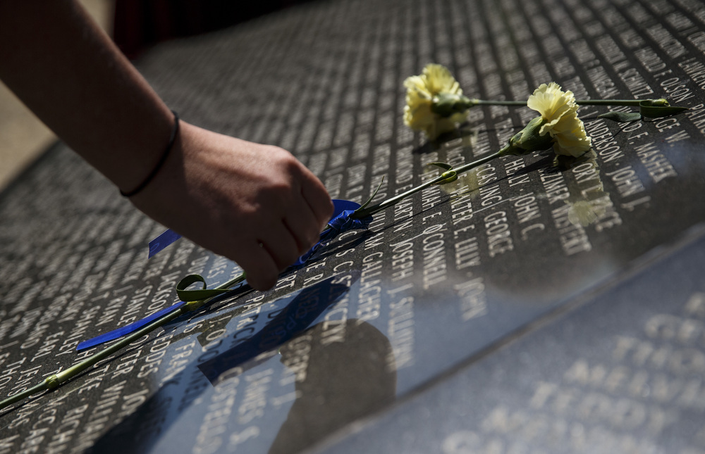 Carnations are left behind by friends and family on the names of fallen officers that are engraved in the base of the Illinois Police Officers Memorial during the 31st annual Police Officer Memorial Day on the grounds of the Illinois State Capitol, Thursday, May 5, 2016, in Springfield, Ill. Justin L. Fowler/The State Journal-Register