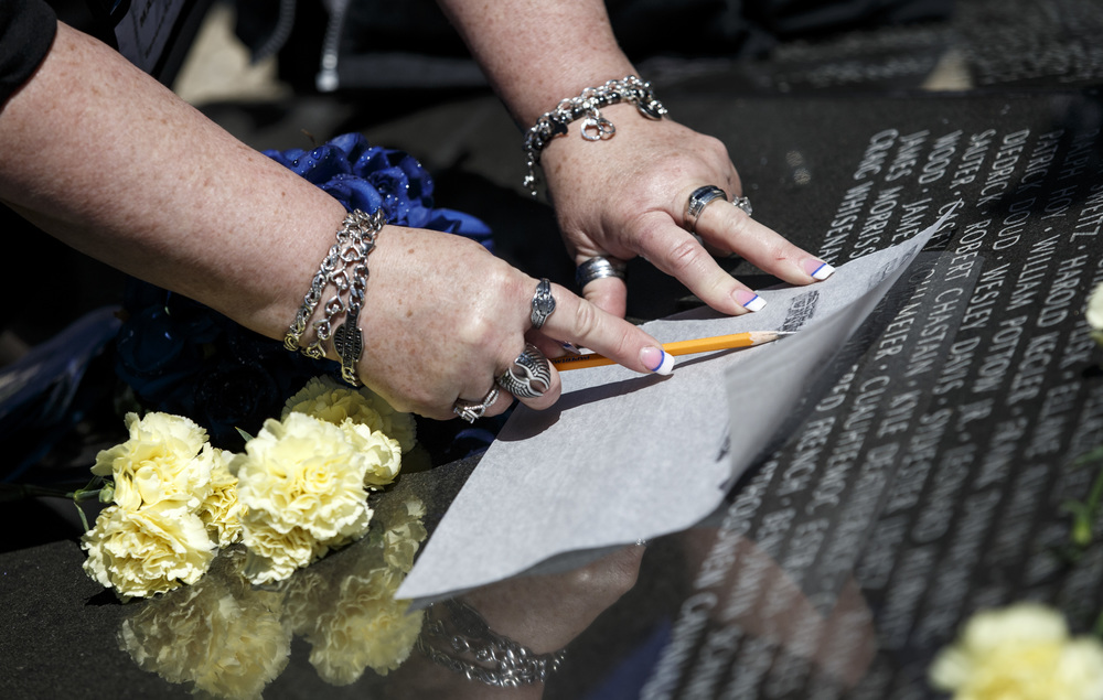 Sue Maness traces out the name of her late husband, Deputy Sheriff Dwight Maness of the McHenry County Sheriff's Office, at the base of the Illinois Police Officers Memorial during the 31st annual Police Officer Memorial Day on the grounds of the Illinois State Capitol, Thursday, May 5, 2016, in Springfield, Ill. Justin L. Fowler/The State Journal-Register