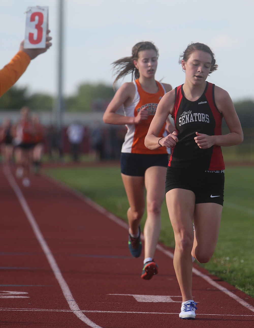 In the third lap of the 3200 meter run, Springfield High School's Natalie Motor gets past Rochester's Madeline Campbell en route to winning the event in 11:45.67 minutes. David Spencer/The State Journal-Register