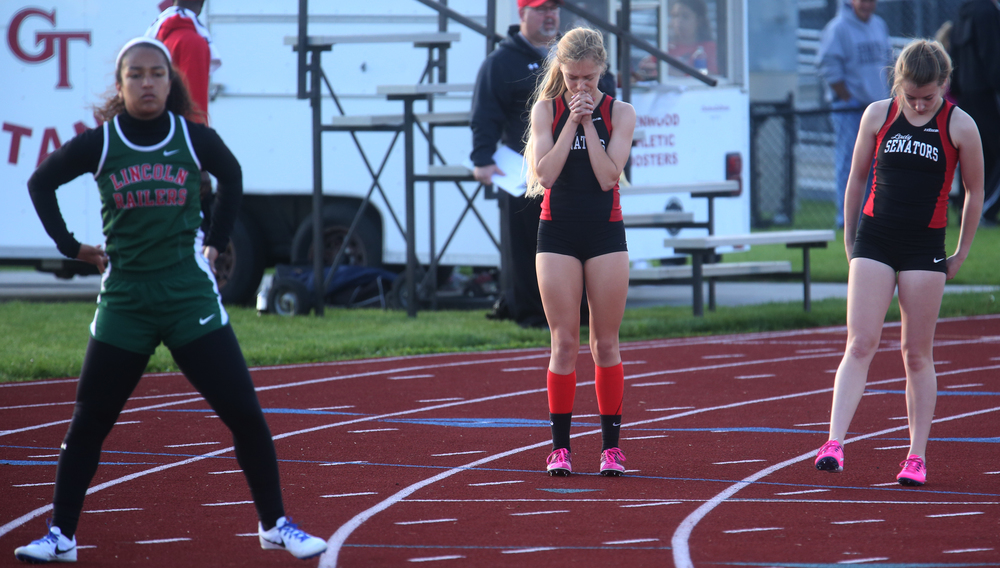 Springfield High School's Aly Goff at center said a prayer moments before she won the 800 meter run event. David Spencer/The State Journal-Register