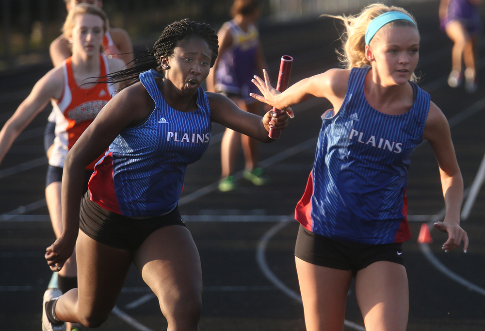 In the girls 4 x 200 meter run, Pleasant Plains runners execute a handoff in route to coming in second in the race to winner New Berlin. David Spencer/The State Journal-Register