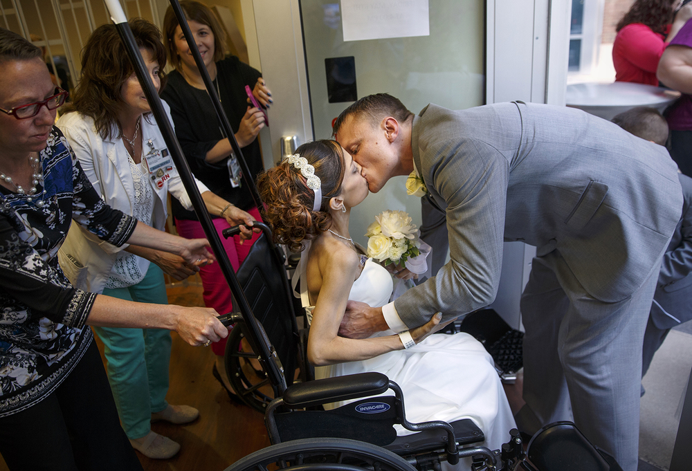 Brandon Thomas kisses his new bride Destini Schafer after easing her into a wheelchair to rest after their wedding ceremony in the courtyard at Memorial Medical Center Friday, May 6, 2016. Nurses at the hospital organized the ceremony after Schafer mentioned her plans to get married even after being told to consider hospice care for her stage four stomach cancer. Ted Schurter/The State Jurnal-Register