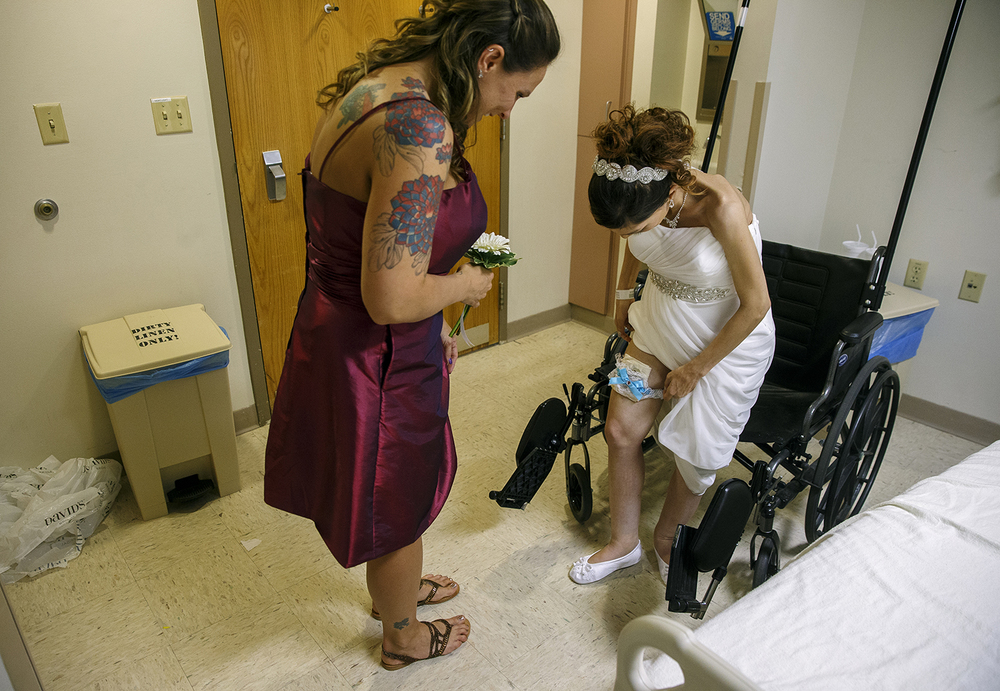 Destini Schafer shows her Maid of Honor Tiffany Gribbins the flask attached to her garter belt before her wedding ceremony at Memorial Medical Center Friday, May 6, 2016.  Ted Schurter/The State Journal-Register