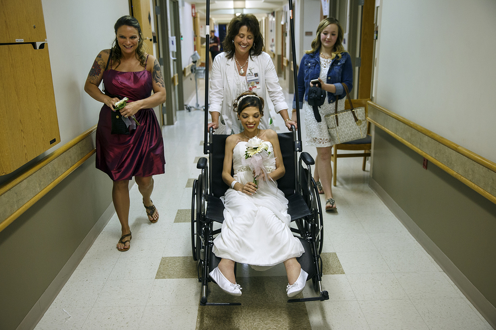 Flanked by Maid of Honor Tiffany Gribbons, left, and Kloee Schmulbach on the right, Destini Schafer is pushed through the halls of Memorial Medical Center to her wedding ceremony to Brandon Thomas Friday, May 6, 2016. Ted Schurter/The State Journal-Register
