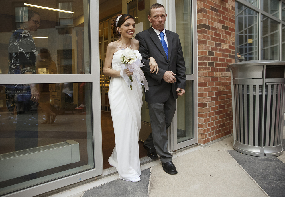 Destini Schafer smiles as she is escorted into a courtyard at Memorial Medical Center by Mike Thomas and glimpses her future husband Brandon Thomas during a wedding ceremony May 6, 2016. The wedding was organized by nurses at the hospital for Schafer who learned two weeks ago that she has stage four stomach cancer. Ted Schurter/The State Journal-Register
