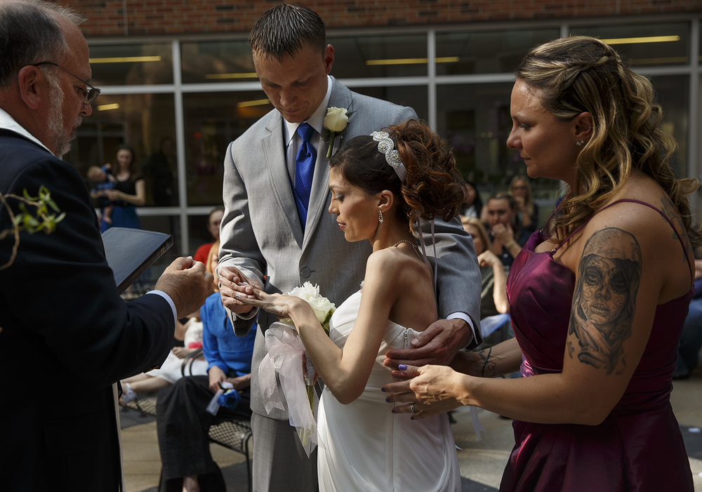 Brandon Thomas places a wedding ring on the finger of his bride Destini Schafer during their wedding ceremony in a courtyard at Memorial Medical Center Friday, May 6, 2016. Ted Schurter/The State Journal-Register