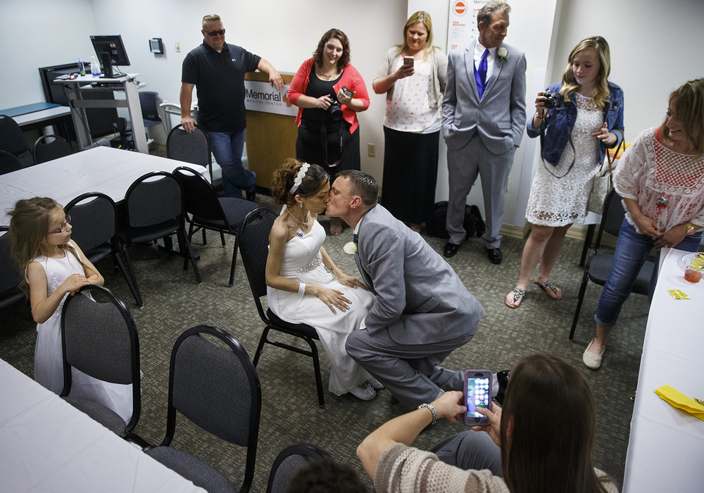 Brandon Thomas kisses Destini Schafer after removing her garter belt during their wedding reception at Memorial Medical Center Friday, May 6, 2016.  Ted Schurter/The State Journal-Register