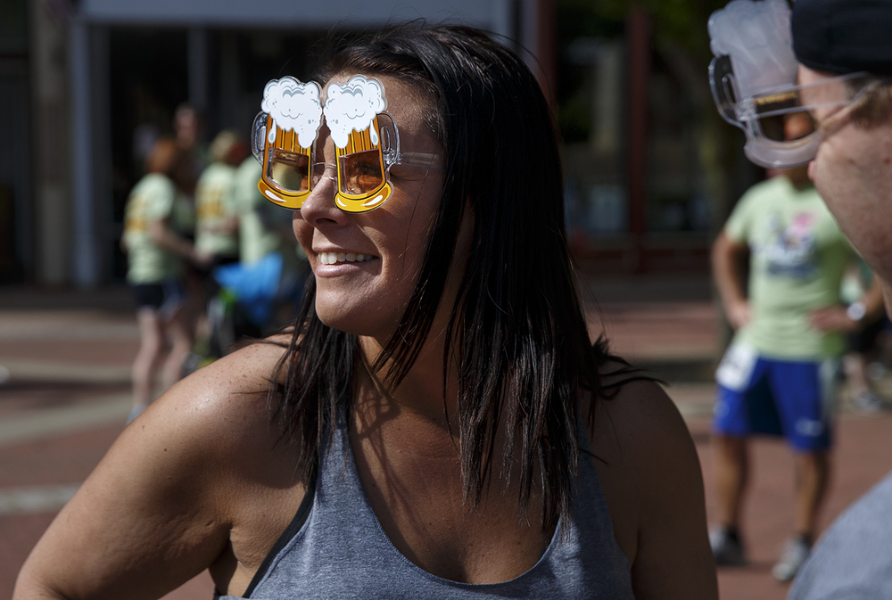 Amber Johnson of Peoria sports a pair of mug-themed sunglasses before the Fat Ass 5K in downtown Springfield Saturday, May 7, 2016. Ted Schurter/The State Journal-Register