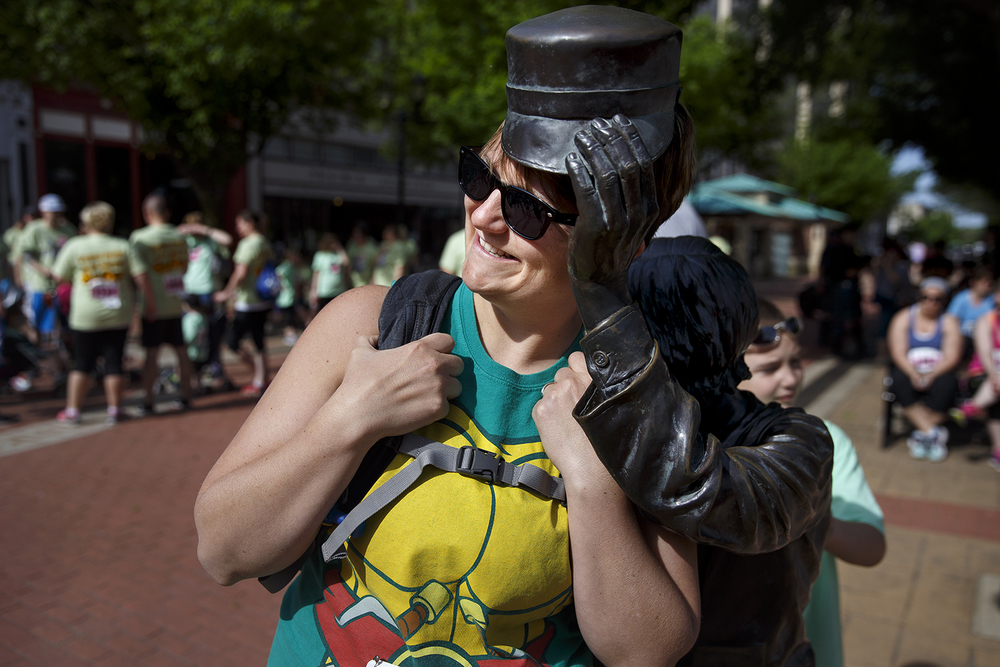 Melissa Hunt is just the right size to pose under the uplifted hat of the Willie Lincoln statue on the Old State Capitol plaza before the Fat Ass 5K in downtown Springfield Saturday, May 7, 2016. Ted Schurter/The State Journal-Register