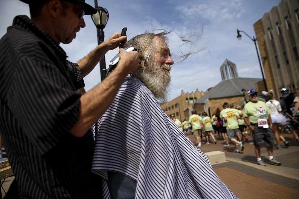 Phil Tackett of Beggs Barber Shop cuts Dan Rothe's hair during the Fat Ass 5K in downtown Springfield Saturday, May 7, 2016. Rothe didn't know the barbers would be on course but took advantage of the opportunity to get his hair cut for the first time in a year. Ted Schurter/The State Journal-Register