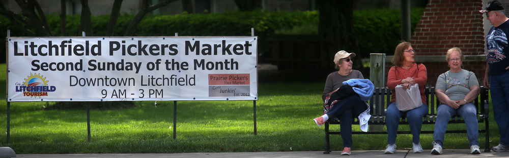 Market patrons take a breather on a bench near the entrance to the market along State Street in downtown Litchfield on Sunday. David Spencer/The State Journal-Register
