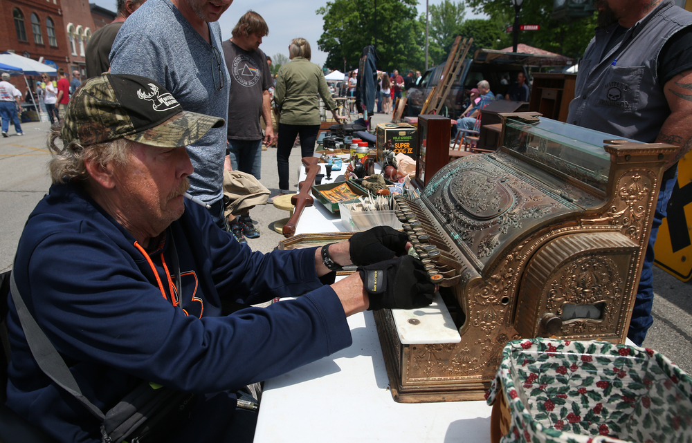 Market vendor Tom Lennox of Mt. Zion attaches a $350.00 asking price on a brass National cash register from the 1930's. David Spencer/The State Journal-Register
