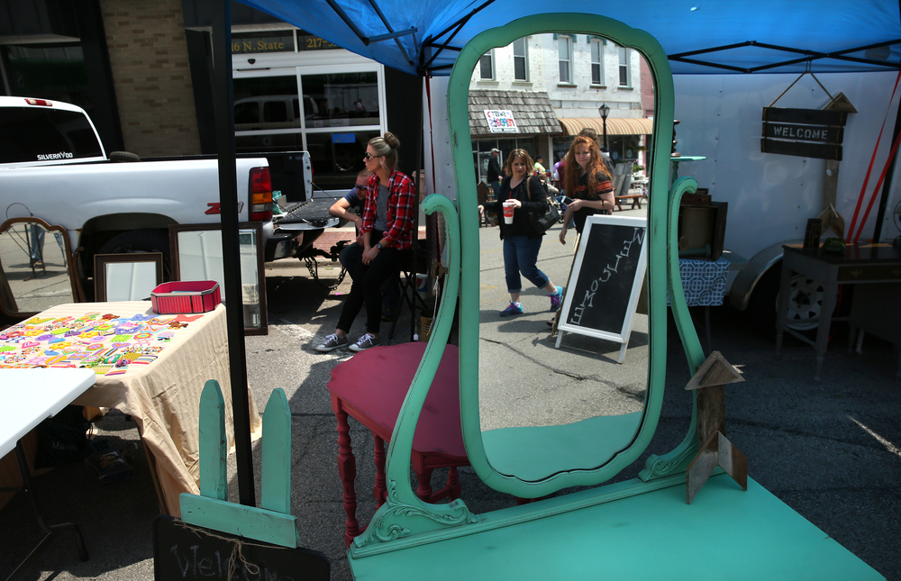 A repainted antique dresser with mirror reflects market patrons walking along State St. on Sunday. David Spencer/The State Journal-Register