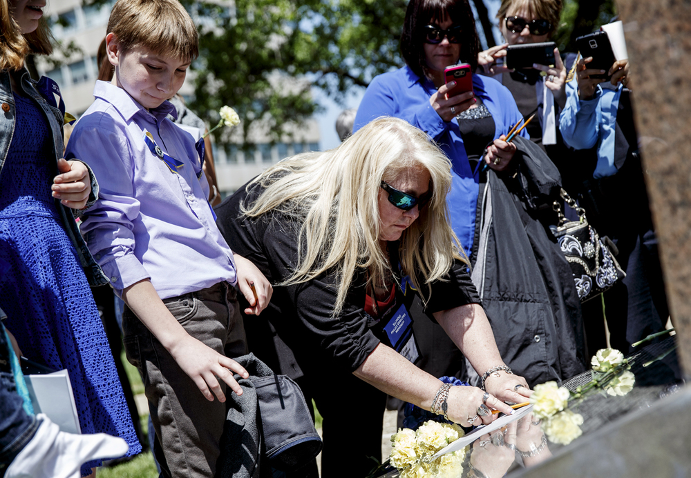 Sue Maness, center, traces out the name of her late husband, Deputy Sheriff Dwight Maness of the McHenry County Sheriff's Office, along with his son, Nicholas, 13, left, at the base of the Illinois Police Officers Memorial during the 31st annual Police Officer Memorial Day on the grounds of the Illinois State Capitol, Thursday, May 5, 2016, in Springfield, Ill. Justin L. Fowler/The State Journal-Register