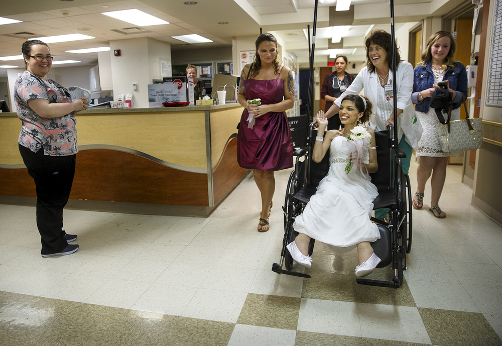 Destini Schafer waves to the nurses at the nursing station at Memorial Medical Center as she is wheeled to her wedding ceremony Friday, May 6, 2016. Ted Schurter/The State Journal-Register
