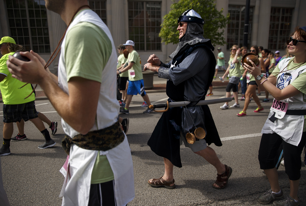 Accompanied by a soundtrack of empty coconut halves banging together, Ken Hovey rides as a Monty Python inspired King Arthur during the Fat Ass 5K in downtown Springfield Saturday, May 7, 2016. Ted Schurter/The State Journal-Register