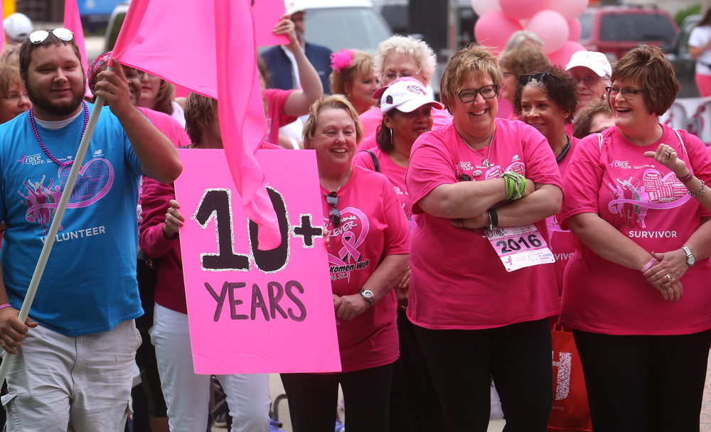 A procession of breast cancer survivors, including women seen here celebrating 10 years or more, walked together as a group to a staging area near the Lincoln statue at Second St. and Capitol Ave. before the start of the race. The procession featured survivors still fighting to those who have gone more than 40 years with the disease. David Spencer/The State Journal-Register