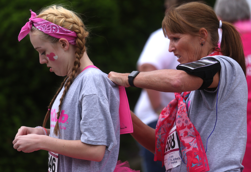 Runner Diane Muncy of Springfield at right pins a race bib in honor of breast cancer fighter Lisa Cannon on the back of her granddaughter Audrey Benedict, who was also getting ready to run Friday night. David Spencer/The State Journal-Register