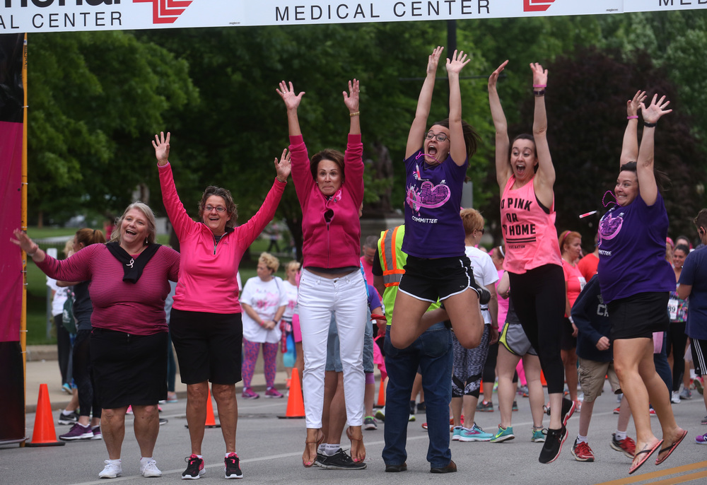Race organizers and participants jump in unison for a photo at the starting line before the official start took place Friday night. David Spencer/The State Journal-Register